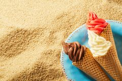 Crispy wafer cones with ice cream against sand stock photo