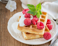 Crispy wafers with cream and fresh raspberries for. Breakfast on a ceramic plate with a sprig of oregano on a wooden background. selective Focus Stock Photography