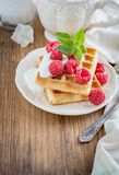 Crispy wafers with cream and fresh raspberries for. Breakfast on a ceramic plate with a sprig of oregano on a wooden background. selective Focus Royalty Free Stock Photos