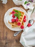 Crispy wafers with cream and fresh raspberries for. Breakfast on a ceramic plate with a sprig of oregano on a wooden background. selective Focus Royalty Free Stock Photo