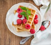 Crispy wafers with cream and fresh raspberries for. Breakfast on a ceramic plate with a sprig of oregano on a wooden background. selective Focus Royalty Free Stock Images