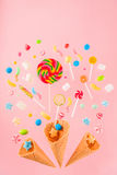 Crispy waffle cones and mix of delicious sweets on pink Stock Photography