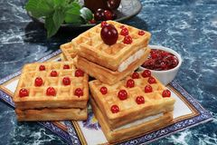 Crispy waffles with berries on a sunny table. Morning breakfast with waffles, currants and milk on a blue background. Selective focus stock photo