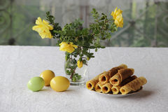Crispy waffles and a bouquet of roses and Easter eggs. Easter eggs, crisp waffles and a bouquet of yellow roses Royalty Free Stock Image