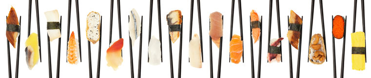 Criss-Crossed Sushi. 18 different types of sushi being held up in in a criss-cross line with black chopsticks isolated on white Stock Image