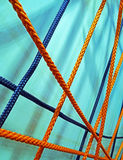 Crisscross tighted colorful ropes. Crisscross tighted orange and blue colored ropes stock photo