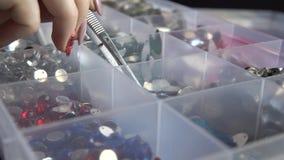 Cristais de rocha coloridos da decoração em uma caixa plástica A mulher está tomando um com pinça filme