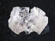 cristal áspero da pedra preciosa de Danburite na obscuridade imagens de stock royalty free