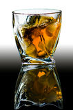 Cristal con los bordes curvados con el viejos whisky escocés y pedazos de hielo foto de archivo libre de regalías
