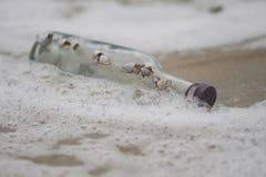 Cristal de botellas en el mar Imagenes de archivo