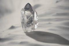 Cristal de cuarzo grande en un primer nevoso del fondo Foto de archivo