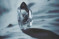 Cristal de cuarzo grande en un primer nevoso del fondo Imagenes de archivo