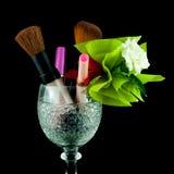 Cristal del vino con los cepillos y los cosméticos del maquillaje aislados en negro foto de archivo