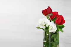 Cristal glass jar with some water and red roses and white flowers. Empty copy space Royalty Free Stock Photo
