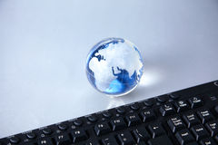 Cristal globe of the Earth on a Computer Royalty Free Stock Image