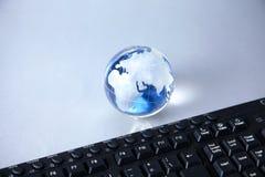 Cristal jordklot av jorden på en dator Royaltyfri Bild