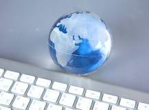 Cristal jordklot av jorden på en dator Royaltyfri Fotografi