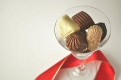 Cristal por completo de chocolates con la cinta roja Fotos de archivo
