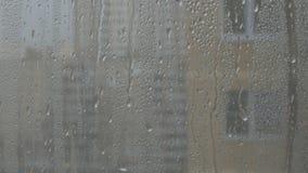Cristal que cae de la lluvia fuerte n del vidrio, gotas de la lluvia que bajan, cielo gris con las casas más allá almacen de video