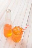 Cristal y paja de botellas de soda anaranjada Imagen de archivo libre de regalías