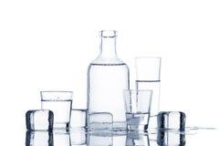 Cristalería con el líquido transparente en la tabla mojada Imágenes de archivo libres de regalías