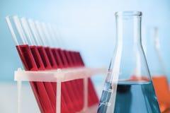 Cristalería de la química en la tabla del laboratorio Fotografía de archivo