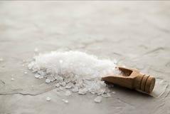 Cristales de la sal del mar en primer de madera de la cucharada en fondo concreto Pequeña pala con la sal del mar Lugar para el t foto de archivo