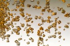 Cristales del oro que caen Imagen de archivo