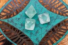 Cristalli naturali dell'ottaedro della fluorite verde sul piatto verde di rame fotografia stock libera da diritti