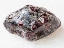 cristalli ruzzolati del granato dell'almandino su marmo bianco Fotografia Stock