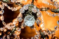 Cristaux d'un lustre élégant avec le fond brouillé du lustre et du plafond d'or Images stock