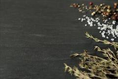 Cristaux, grains de poivre et thym de sel brut sur l'ardoise foncée photo stock