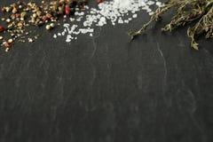 Cristaux, grains de poivre et thym de sel brut sur l'ardoise foncée photographie stock