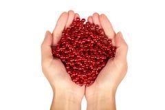 Cristmas装饰,在白色背景在手中隔绝的陶瓷红色球链子 新年对象,狂欢节小珠 库存照片
