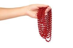 Cristmas装饰,在白色背景在手中隔绝的陶瓷红色球链子 新年对象,狂欢节小珠 免版税图库摄影