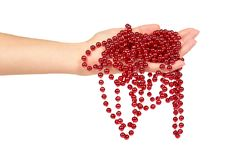 Cristmas decoration, ceramic red ball chain in hand isolated on white background. New Year object, Mardi Gras beads.  Stock Image