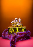 Cristmas gift golden box orange background Stock Photos