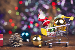Cristmas items. New year gift boxes in shopping cart on wooden background Stock Image