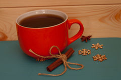 Cristmas theme - big orange tea cup and cinnamon roll Royalty Free Stock Images
