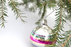 A Cristmas tree branch with a glass ball. On a white background Royalty Free Stock Photo