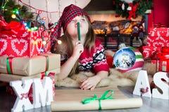 Cristmas wish list. Girl reflects on gift list Stock Photos
