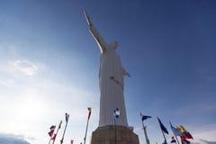 Cristo del Rey staty av Cali med världsflaggor och blå himmel, sänka Arkivfoto