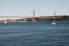 Cristo la statua ed il 25 aprile di re getta un ponte su sopra il Tago a Lisbona, Portogallo Immagini Stock Libere da Diritti