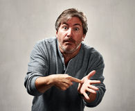 Critical angry man. Critical blaming man portrait over gray wall background Stock Photos