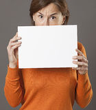 Critical middle aged woman hiding behind scary blank communication board. Critical middle aged woman hiding behind a scary blank communication board to alert or royalty free stock photos