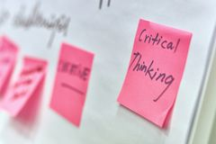 Critical thinking written on pink paper stickers attached to a flip chart stock photos