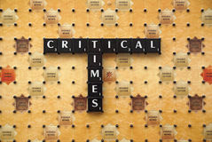 Critical Times tiles. Critical times spelt out on a Scrabble Board. Picture is good to use as a background picture to highlight the times we live in Royalty Free Stock Photos