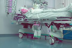 Critically ill patient connected to vital apparatus in the advan. Ced bed of intensive care unit royalty free stock photos
