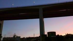 Criticando de debajo del puente ic?nico del 25 de abril en Lisboa, Portugal en la puesta del sol con colores magentas y rosados e almacen de video
