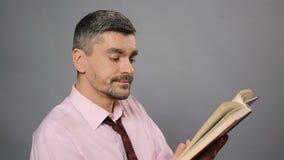 Critico letterario che si siede alla biblioteca, leggente libro asciutto e sbadigliante, romanzo d'alesaggio stock footage